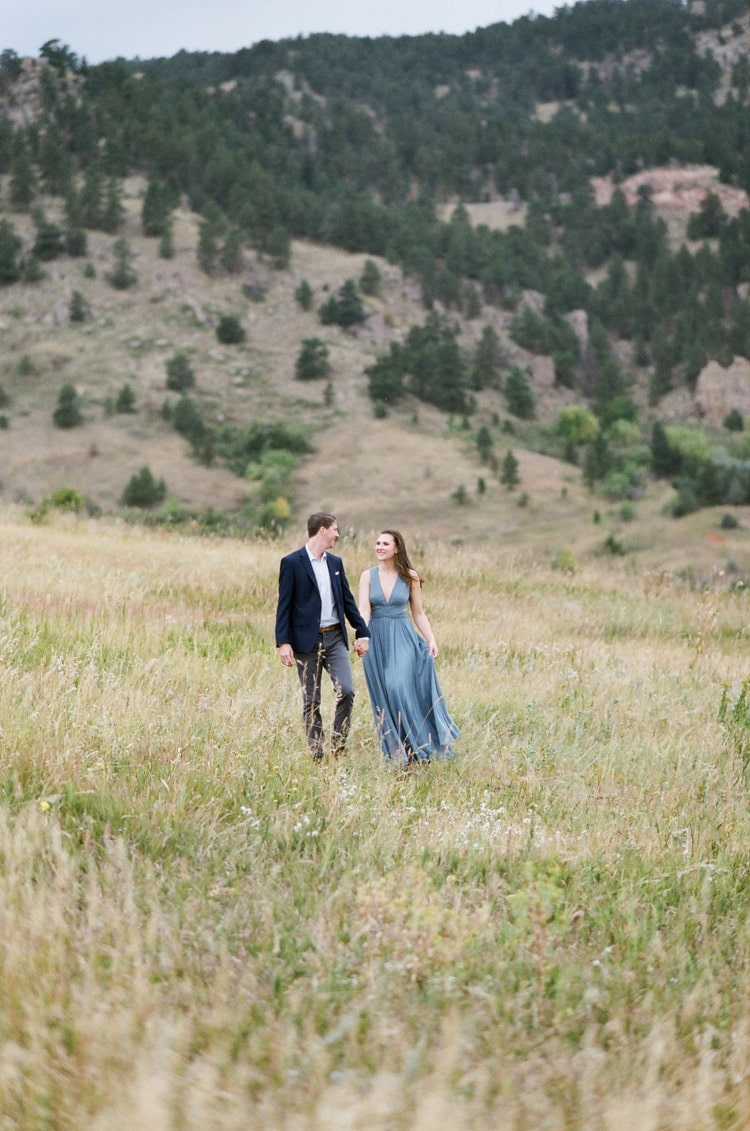 Engaged couple walking together in grass fields with pine trees in backdrop