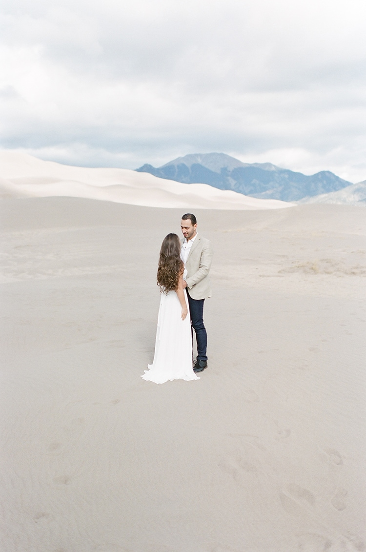 Engaged couple at the Great Sand Dunes National Park and Preserve in Colorado with mountain range in background