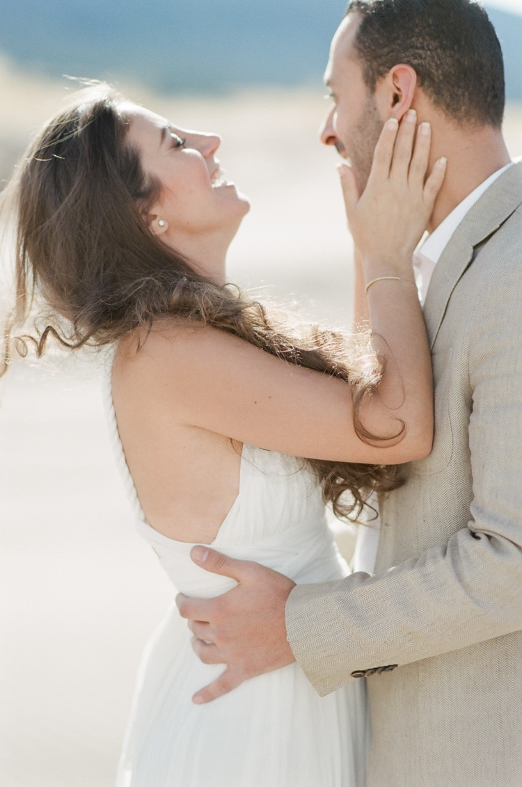 Bride and groom posing for engagement portraits with sand dunes in backdrop