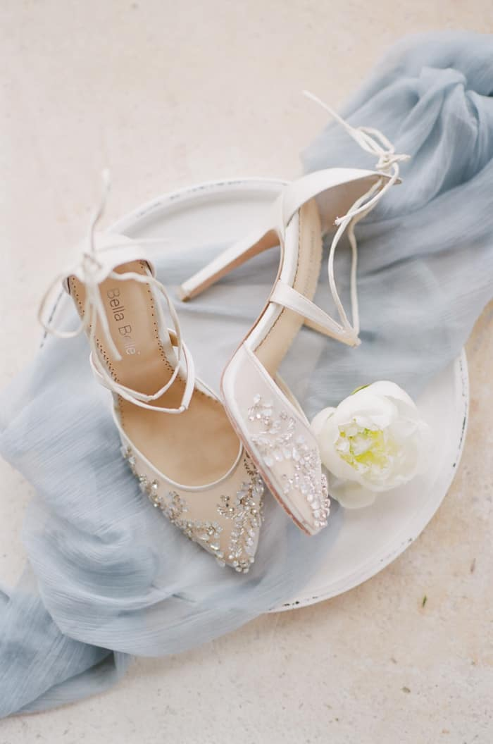 Bella Belle Shoes laying on top of blue mesh and next to white flower