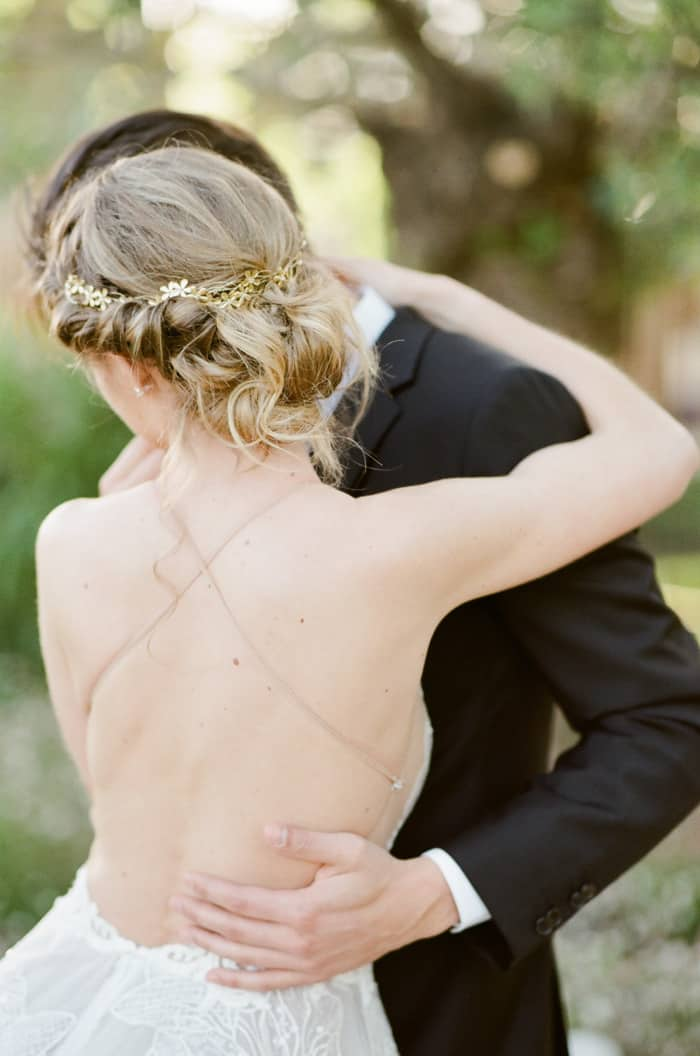 Woman wearing backless wedding dress embracing partner