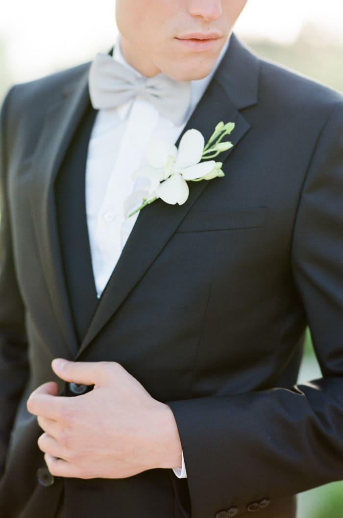 Groom in black suit wearing Boutonniere
