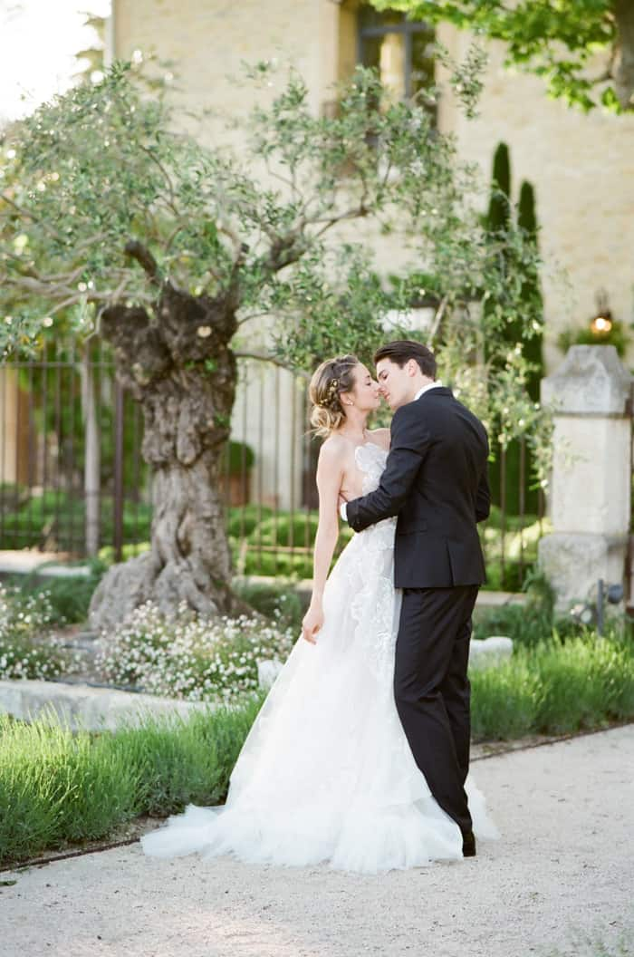 Happy Wedding Couple Kissing in front of olive tree