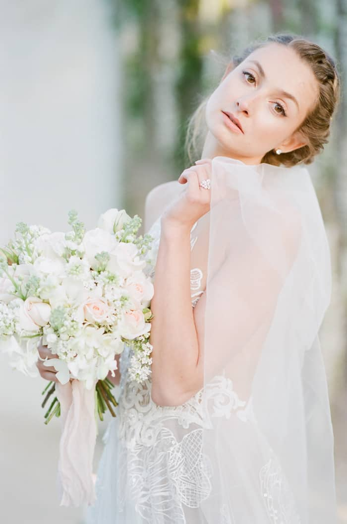 Bride posing in wedding dress with large bouquet of white flowers