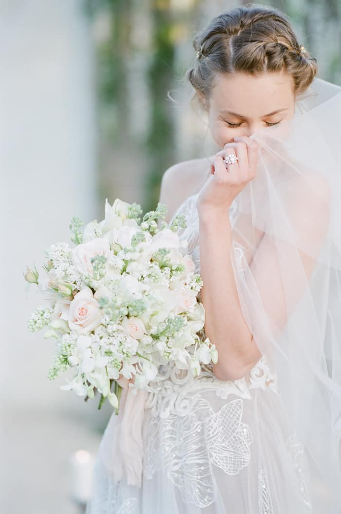 Bride posing and hiding face behind wedding veil