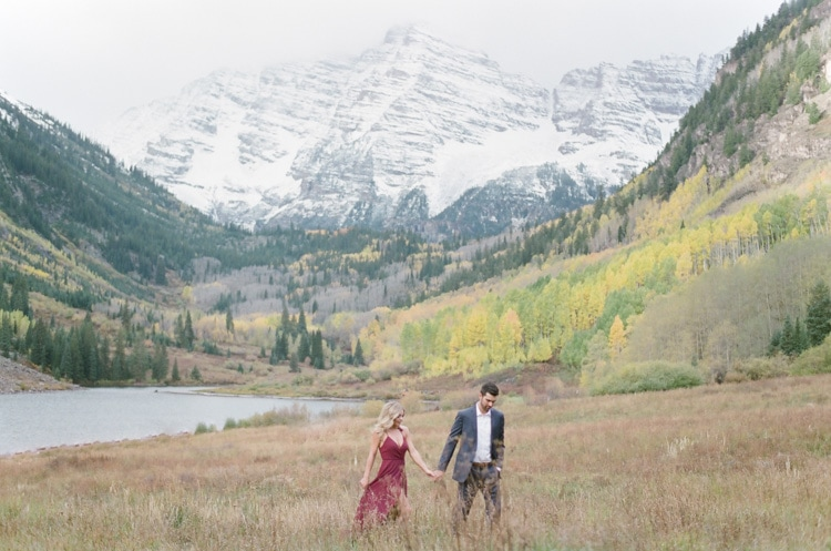 Engaged couple walking together with Maroon Bells in the background