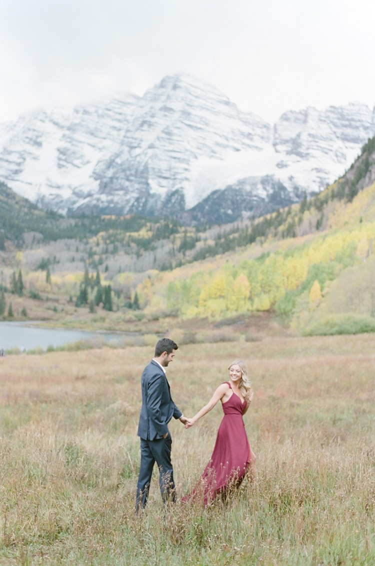 Couple holding hands during portrait session with Colorado mountains in the background