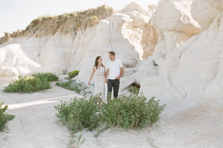 Engaged couple holding hands in front of the Paint Mines during summer evening