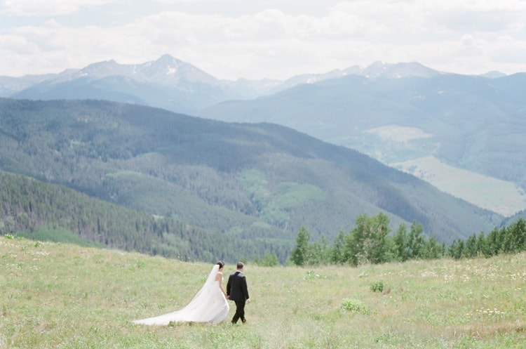 Bride and groom walking in front of the Vail mountains
