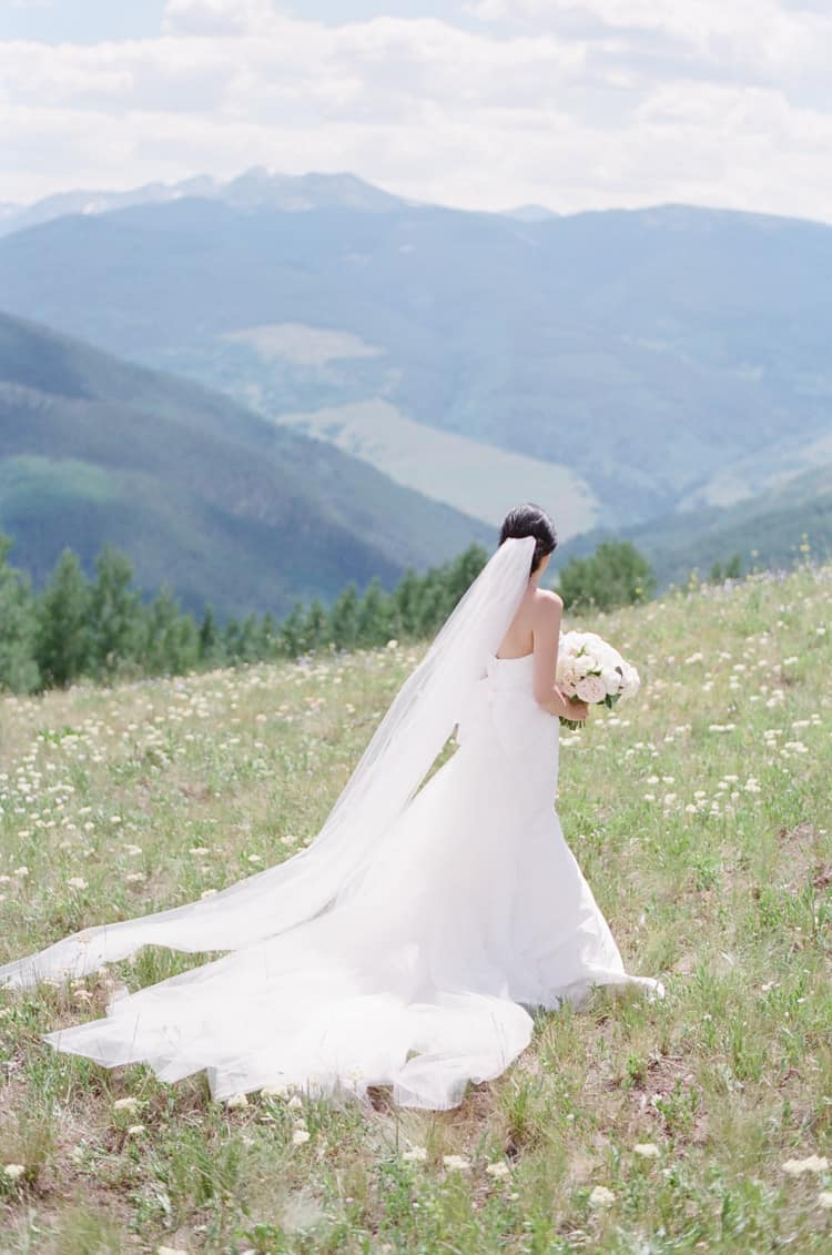 Bride in a wedding dress and long veil look at the mountains in Vail Colorado
