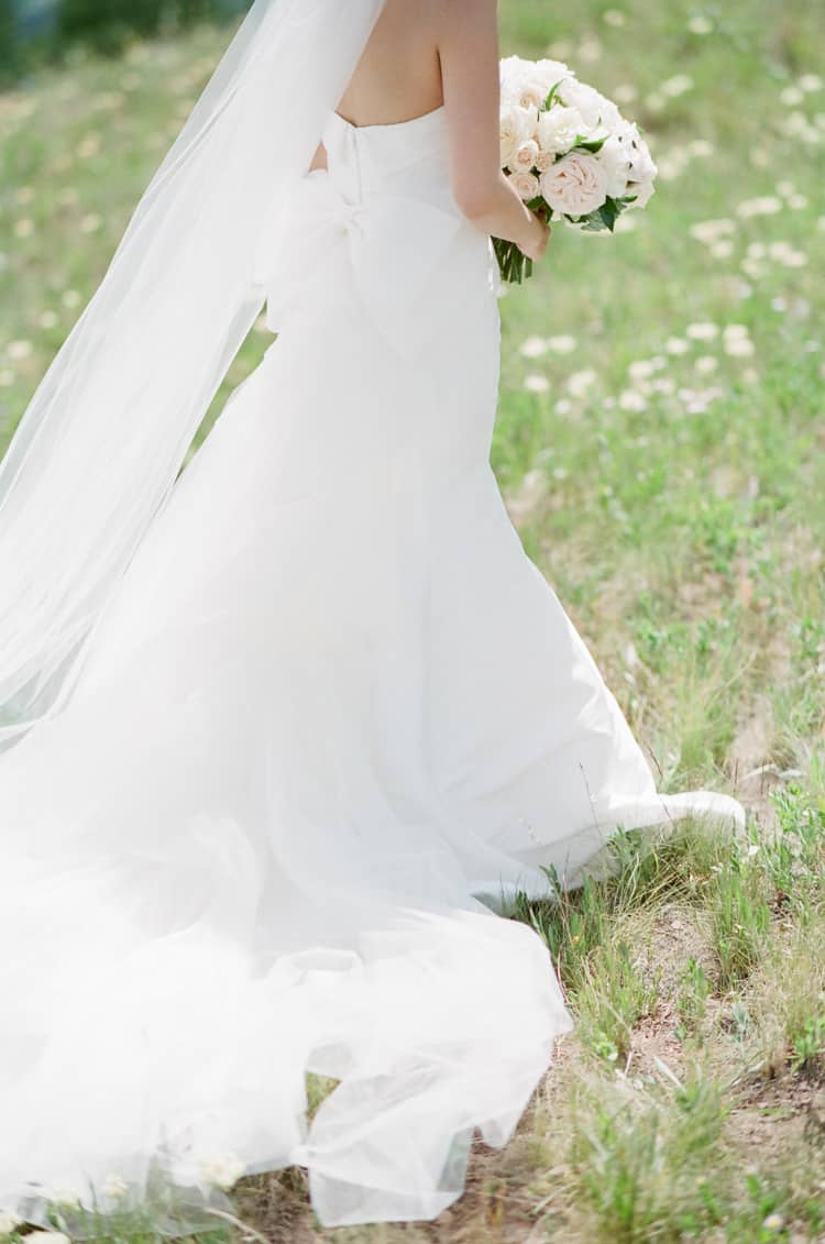 Bride standing in a field holding a bouquet in Vail Colorado