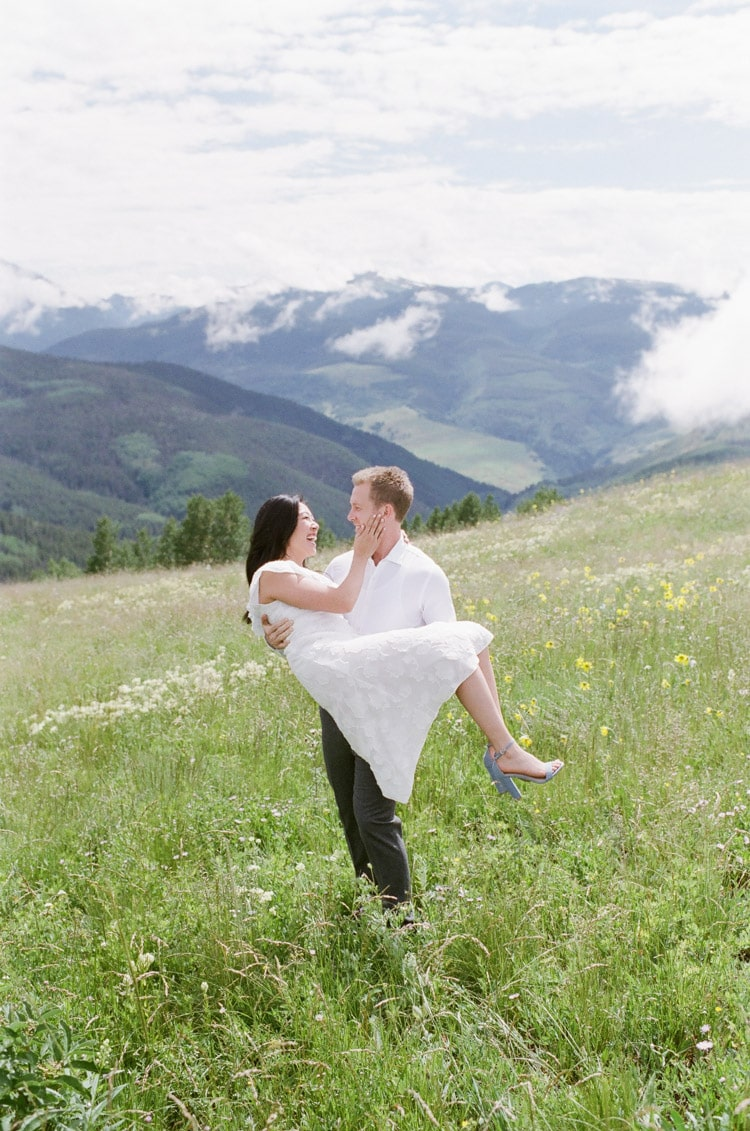 Groom holding Bride with both wearing white clothes and mountains view