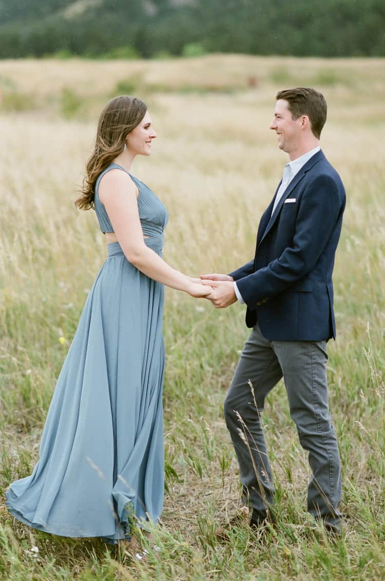 Bride and Groom To Be Facing Each Other In Front Of Flatirons In Boulder Planned By Cloud9 Bliss