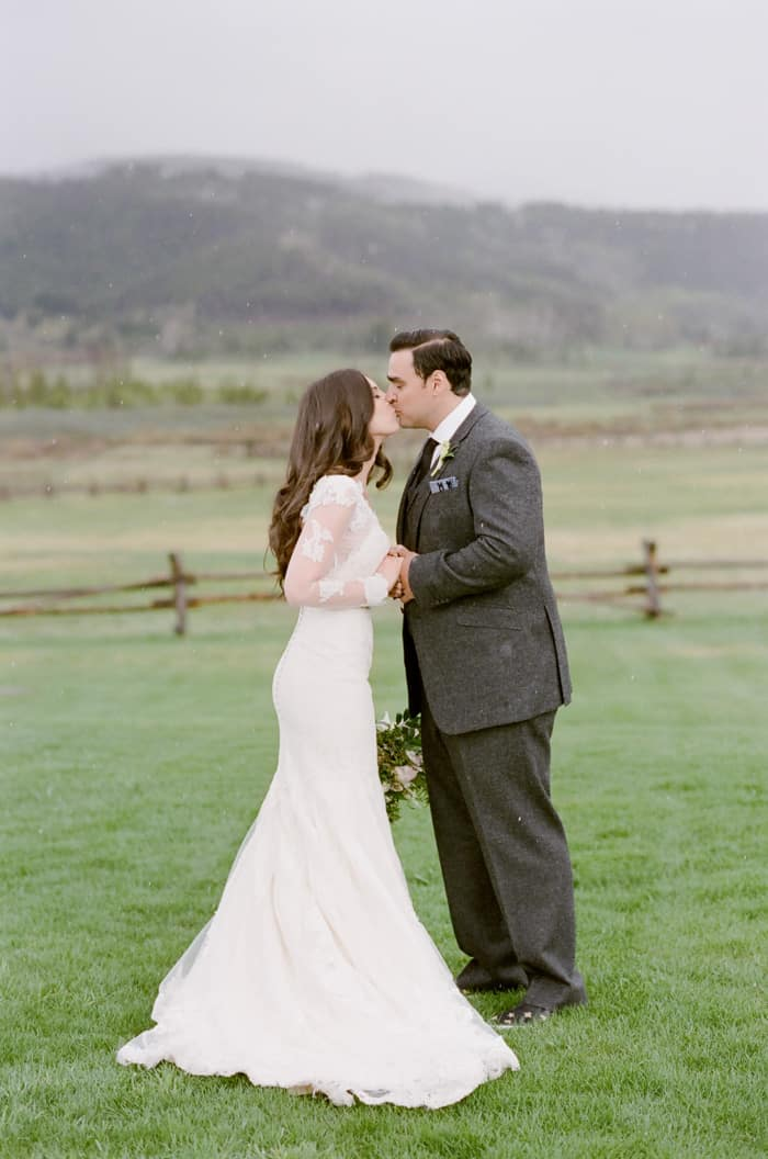 Groom and bride kissing in open field