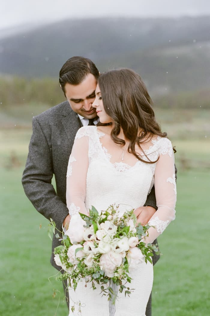 Groom embracing bride from behind with bride holding large bouquet