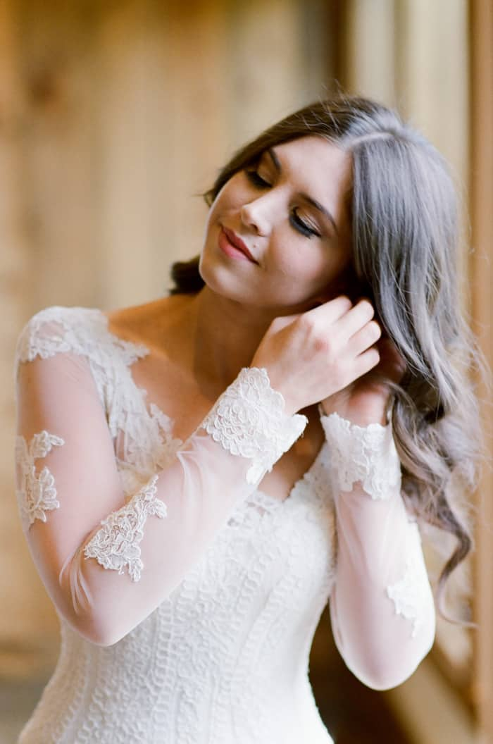 Bride getting ready in long-sleeved lace dress