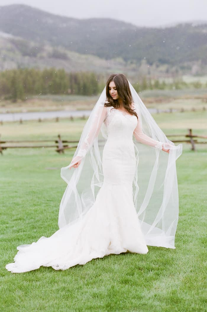 Bride wearing Inbal Dror dress and veil with snow falling