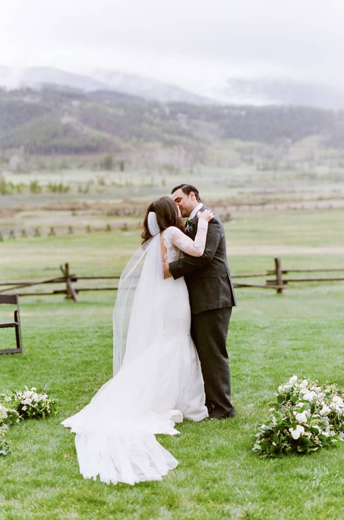Groom & bride's first kiss with Colorado mountains in the backdrop