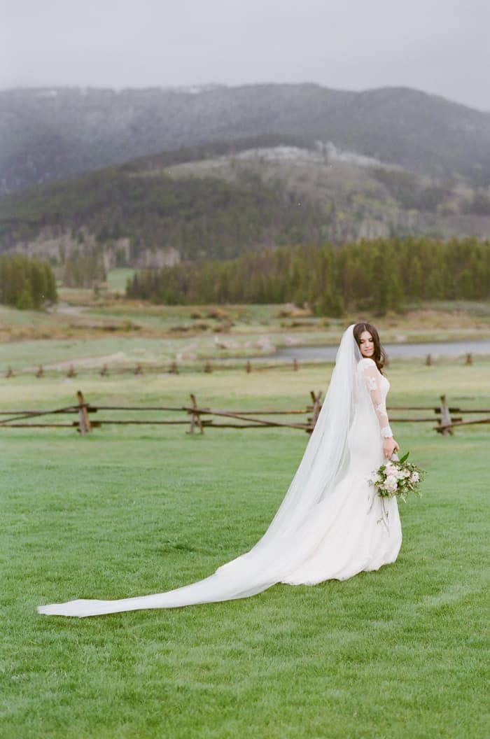 Bride at ranch during her winter wedding with mountain backdrop