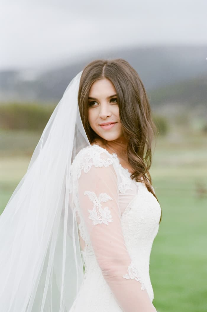 Close up side view of Bride wearing Inbal Dror dress and veil