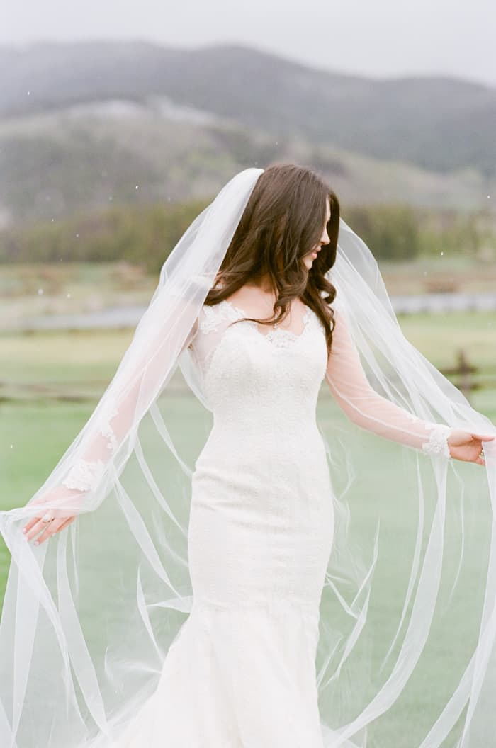 Playful bride wearing lace with veil