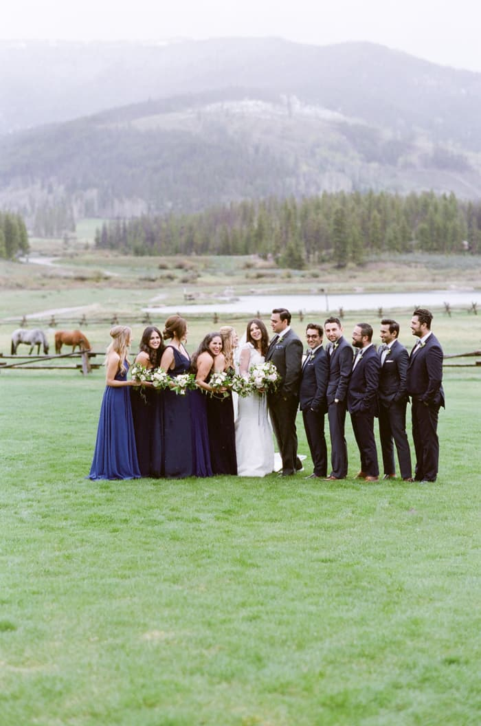 Bridal party laughing together with horses in the background