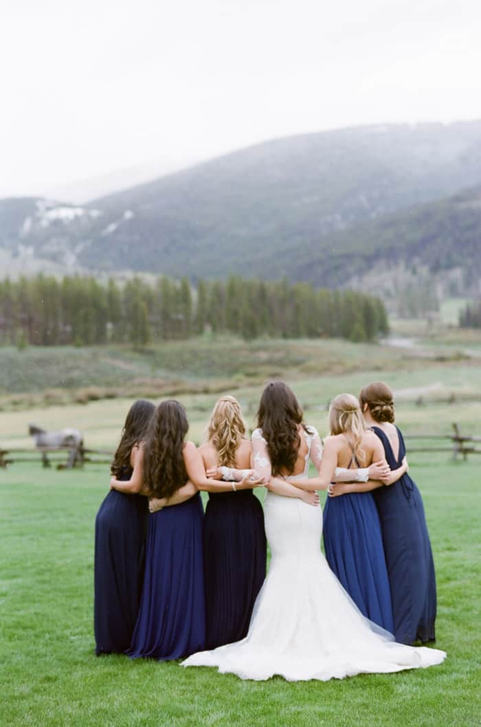 Bride with bridesmaids looking away towards the mountains