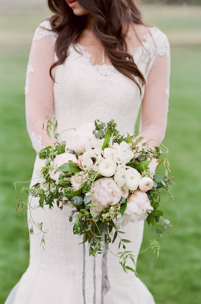 Bride wearing white lace gown holding bouquet with white assortment of flowers