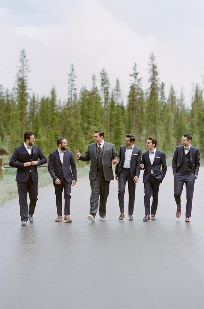Groom walking together with groomsmen with trees in background
