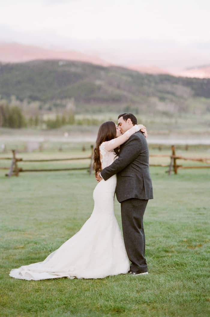 Bride and groom kissing with views of the Colorado mountains in the background