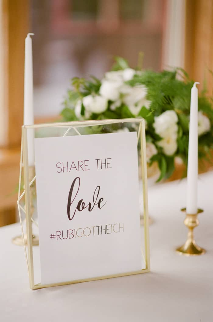 """Sign on table that says """"share the love"""" with custom wedding hashtag"""