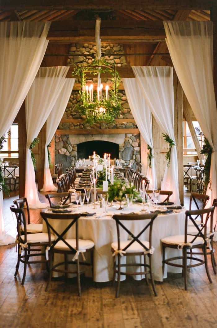 Wedding reception table in front of large stone fireplace with white curtains at Devil's Thumb Ranch