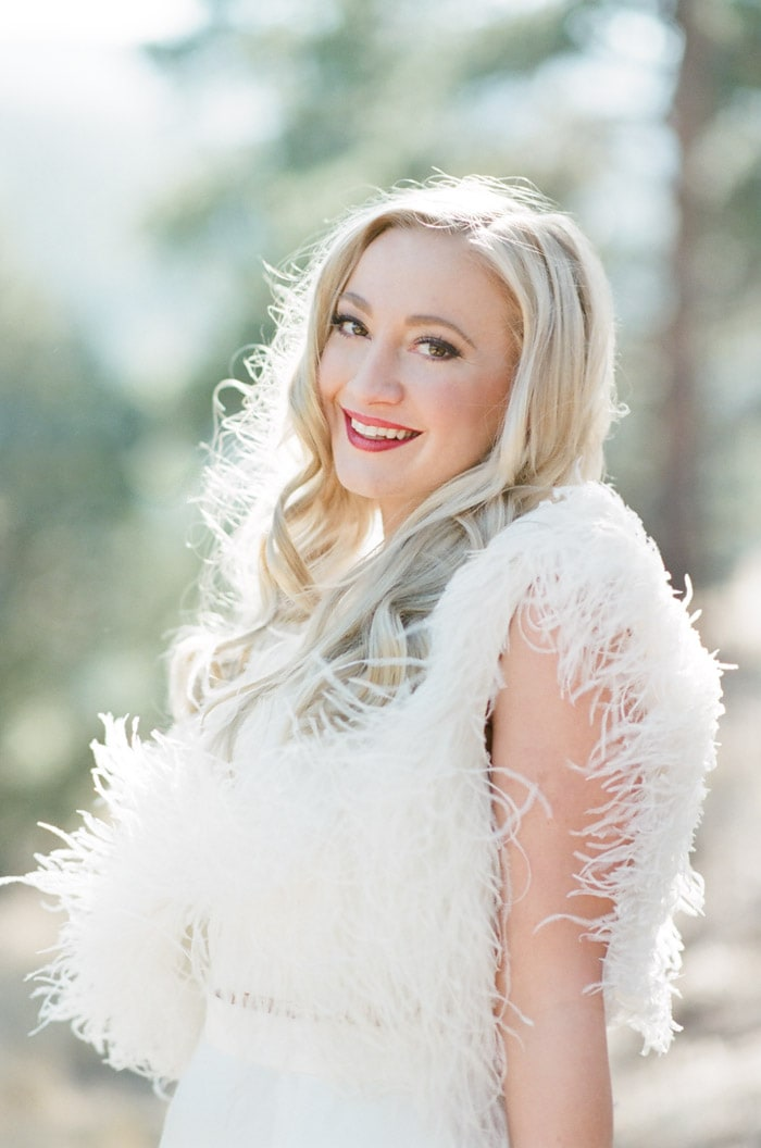 Carly, owner of Denver based Milkglass Productions, wearing white fur jacket
