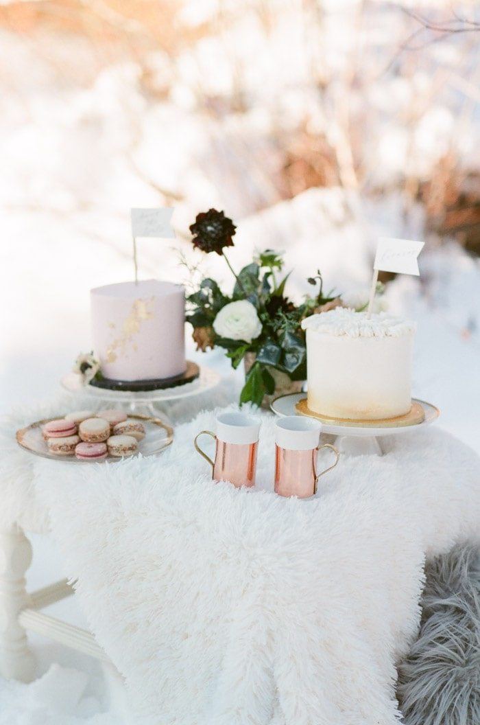 Little table with white fur over it and cakes, macaroons, and coffee on it.