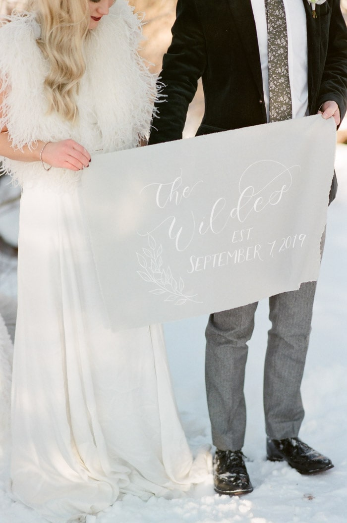 Man & woman holding light grey sign with white calligraphy written on it