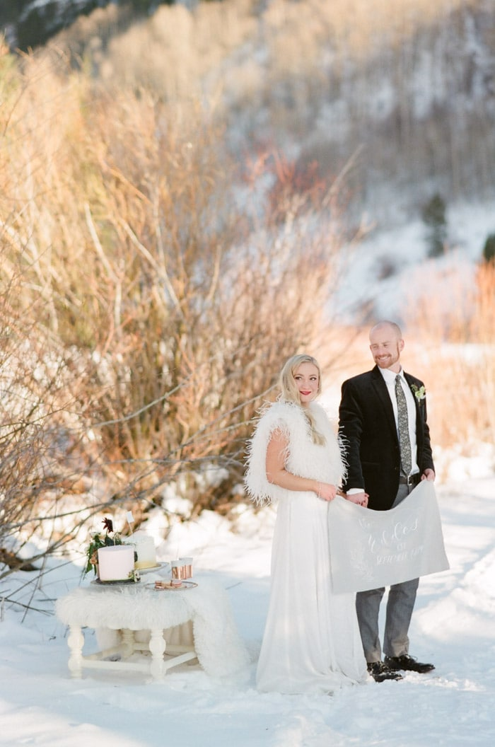 Couple posing in the snow holding sign next to little picnic table