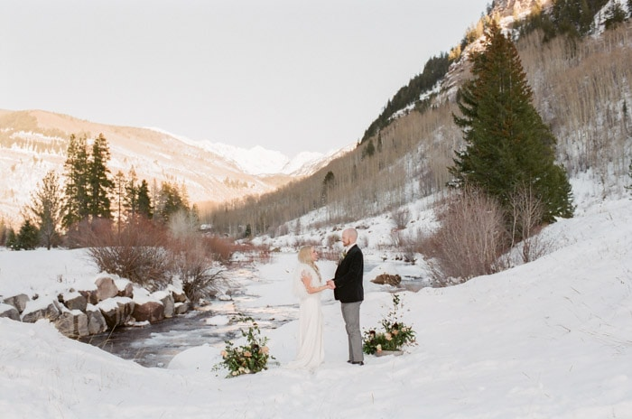 Couple holding hands looking at each other between two floral decoration in the snow and winter view of Vail Valley in background