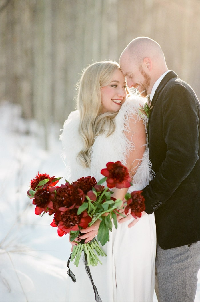 Carly, owner of Milkglass Productions in Denver holding red flowers and embraced by her fiance