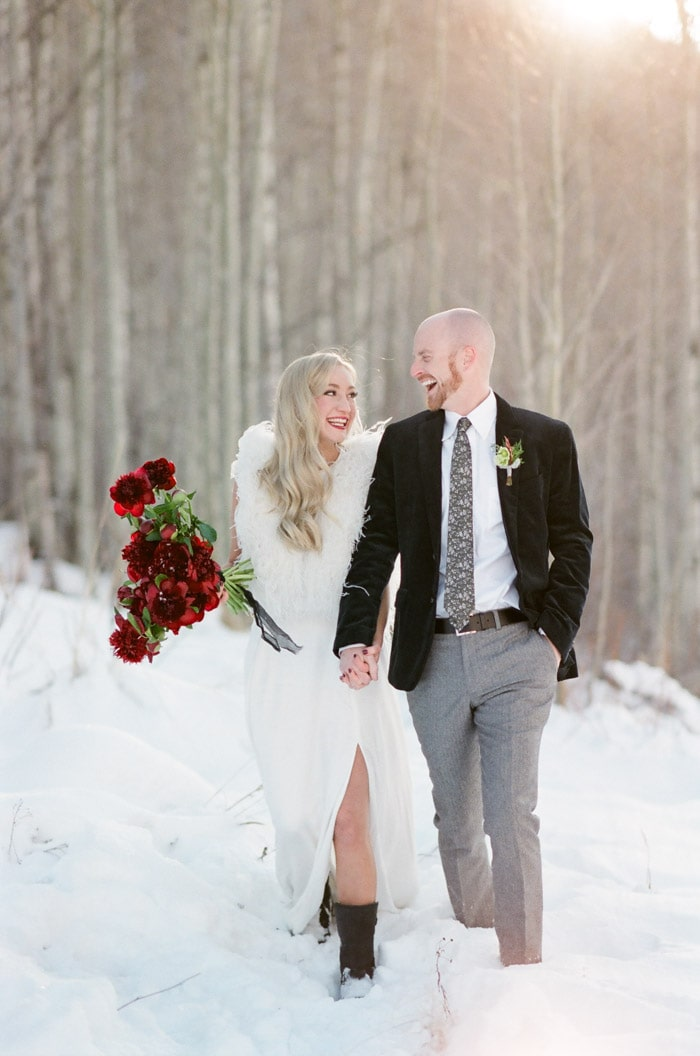 Engaged couple walking together in the snow with men wearing black corduroy jacket with silks satin patterned tie and herringbone pants
