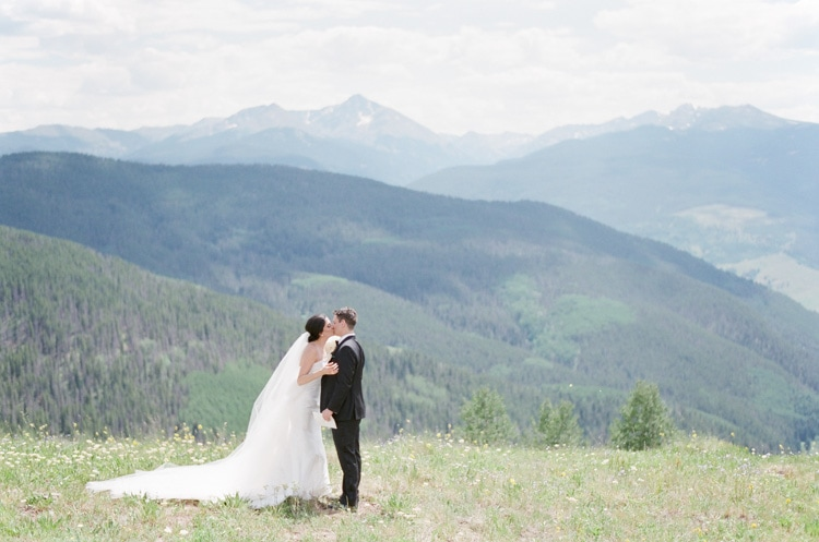 Bride and groom kissing on top of Vail mountain during their first look in Colorado