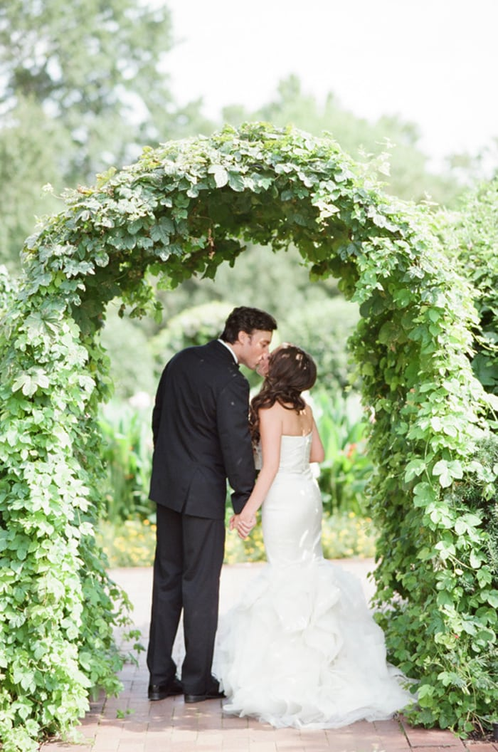 Bride and groom kissing under an arch at the Chicago Botanic Garden