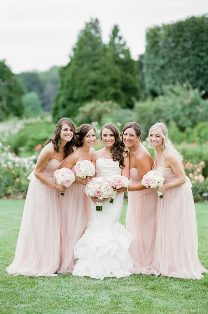 Bride with her bridesmaids in blush pink dresses in the Chicago Botanic Garden