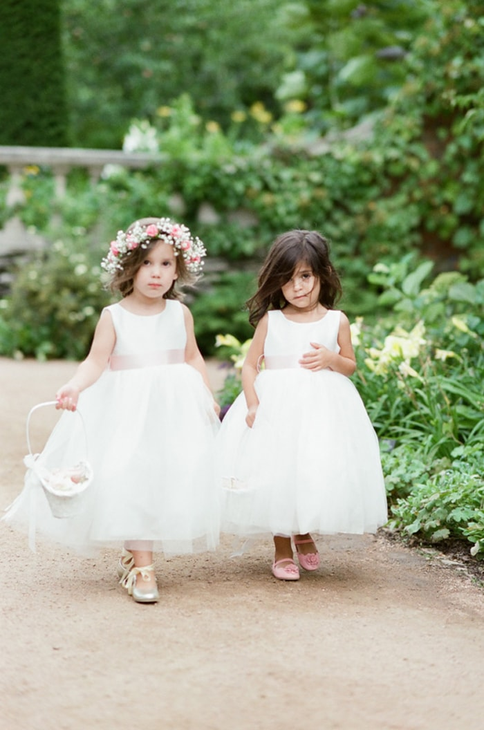 Flower girls walking down the aisle at a wedding ceremony at the Chicago Botanic Garden
