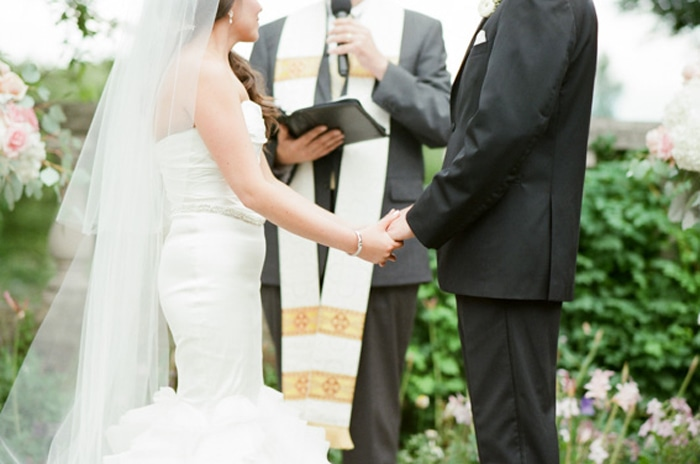 Couple holding hands at the altar for their outdoor wedding at the Chicago Botanic Garden