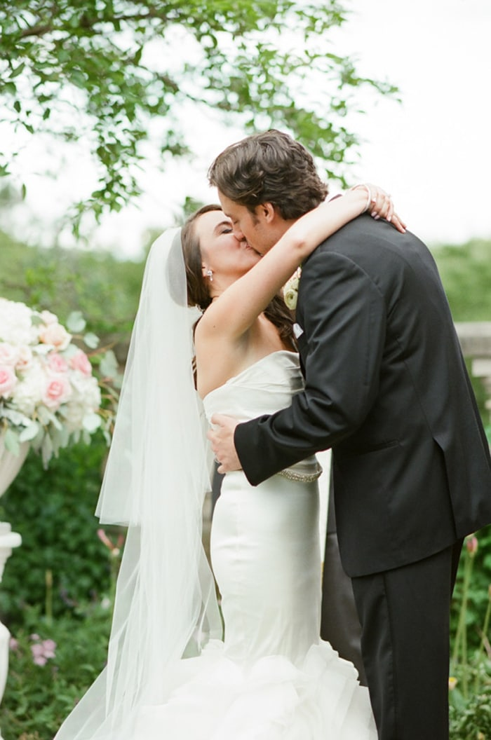 Couple kissing during their outdoor summer wedding at the Chicago Botanic Garden