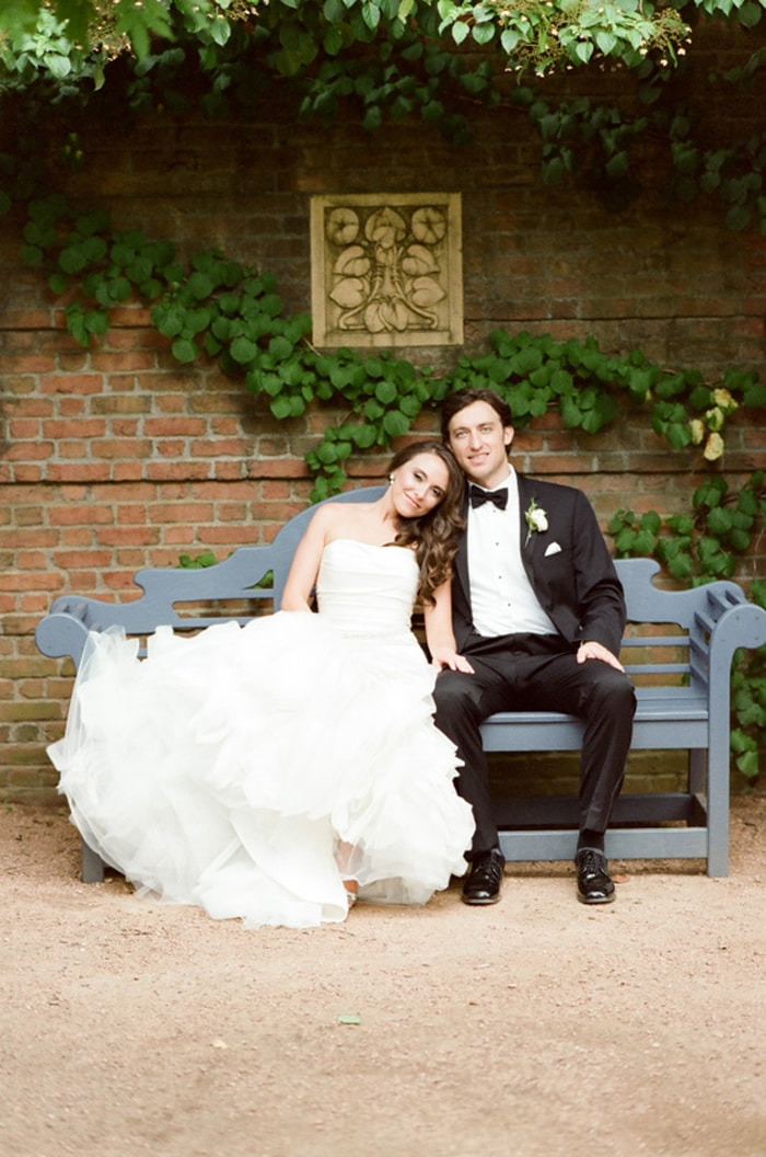 Bride and groom sit on a bench at the Chicago Botanic Garden