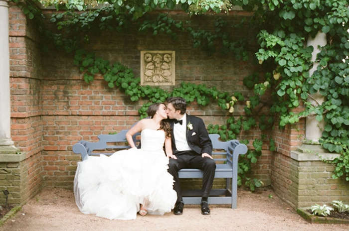 Bride and groom kiss on a bench at the Chicago Botanic Garden