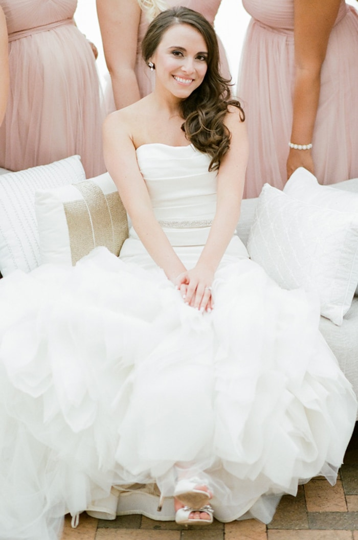 Bride sits on a settee surrounded by her bridesmaids at the Chicago Botanic Garden