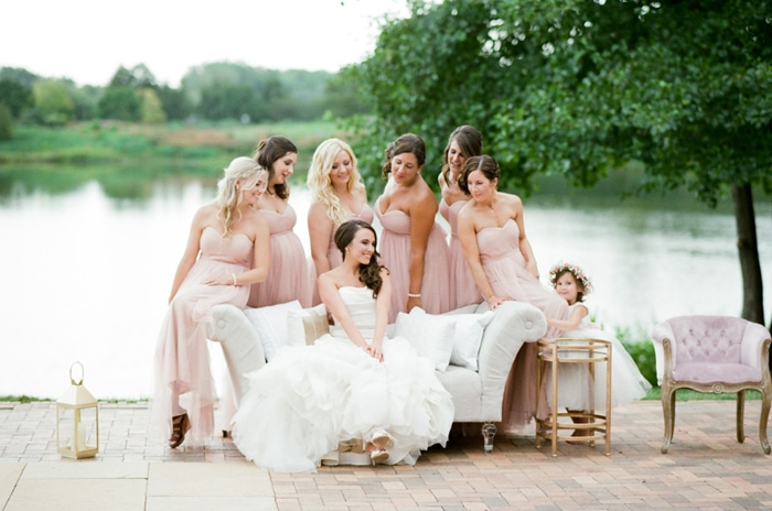 Bride sitting on a sofa with her bridesmaids in the background