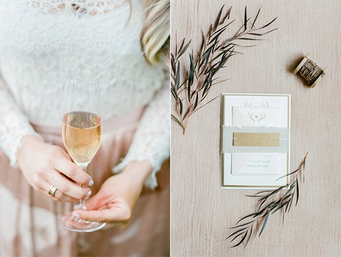 Woman holding a glass of champagne an an invitation suite styled with greenery